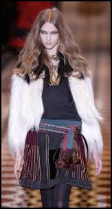 Gucci - Near left - black and white goat pleated jacket with leather trim detail, black wool linen multi-ribbon embroidered skirt and sequoia and brown silk scarf with tassels.