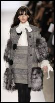 Grey coat with hemline and cuffs trimmed with deep fur bands by Dennis Basso.