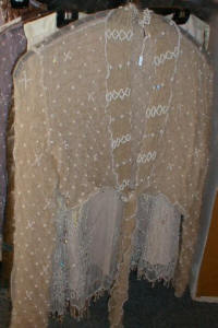 Lace net shrug decorated with cream pearls and beads.