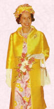 Queen in a straight silk duster coat with contrast print dress